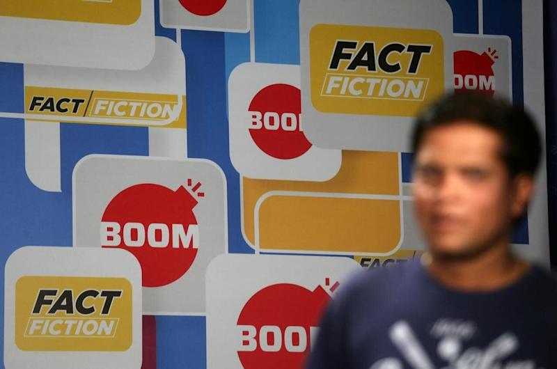 A crew member walks in front of a hoarding displaying the logo of BOOM, one of Facebook Inc's fact-checking partners in India, at a studio in Mumbai, March 12, 2019. Image credit: REUTERS/Francis Mascarenhas/Files