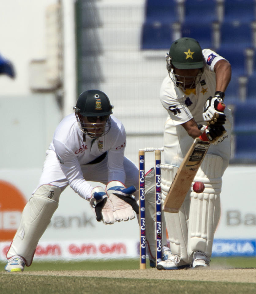 Pakistan batsman Adnan Akmal bats during his first over as South Africa's wicket keeper Ab de Villiers readies for a catch during the third day of their first Test against South Africa at the Sheikh Zayed Cricket Stadium in Abu Dhabi on October 16, 2013. Pakistan were bowled out for 442 in their first innings giving them a lead of 193 runs over South Africa's first innings of 249.  AFP PHOTO/STR        (Photo credit should read -/AFP/Getty Images)