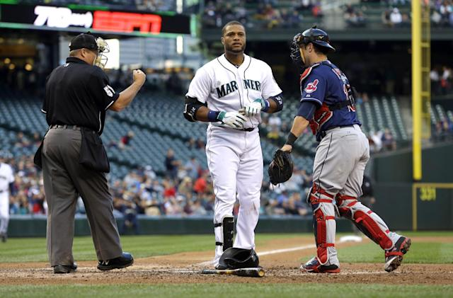 Home plate umpire Marvin Hudson, left, signals Seattle Mariners' Robinson Cano, center, out after he struck out swinging as Cleveland Indians catcher Yan Gomes stands next to them at the end of the fourth inning of a baseball game, Saturday, June 28, 2014, in Seattle. (AP Photo/Ted S. Warren)