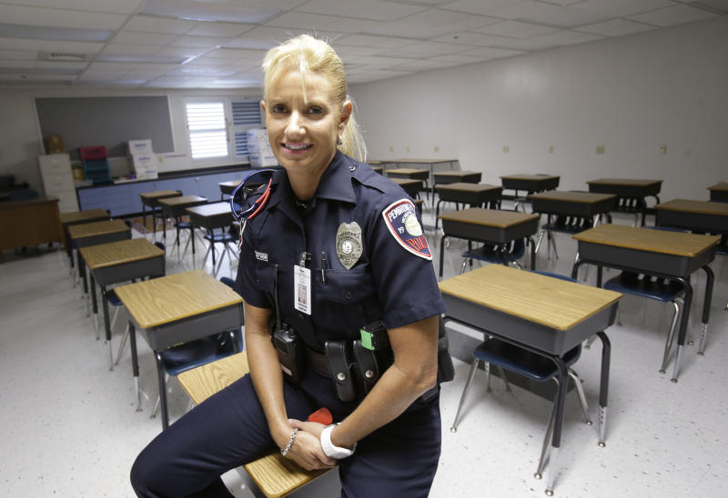 In this photo taken Thursday, Aug. 22, 2013, Dara Van Antwerp, the school resource officer at Panther Run Elementary School Pembroke Pines, Fla., sits in the classroom where she teaches a Gang Resistance And Drug Education (GRADE) program to students in the Fort Lauderdale suburb. The armed school resource office will be permanently stationed on campus despite the decline in crime in this middle-class community. The decision comes in the wake of the Sandy Hook Elementary School shooting in Connecticut. (AP Photo/Wilfredo Lee)