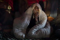 Nathu Singh, an 86-year old farmer, wrapped in a quilt, smokes a bidi, or hand-rolled tobacco, after waking up in the back of his tractor trolley blocking a highway in protest against new farm laws at the Delhi-Uttar Pradesh border, on the outskirts of New Delhi, India, Tuesday, Dec. 29, 2020. (AP Photo/Altaf Qadri)