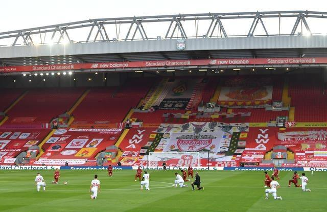 Players from Liverpool and Crystal Palace take a knee in front of an empty Kop