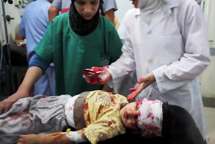 This image taken from video filmed by an independent cameraman and made available on Monday, Sept. 3, 2012 shows Syrian medics helping a wounded child at the Dar al-Shifa hospital, in Aleppo, Syria. Grief stricken parents tried desperately to calm their injured children as the doctors at the Dar al-Shifa hospital struggled to treat an influx of injured in a mortar attack. Local residents say the attack was launched by Syrian government forces onto a densely populated area of the city on Monday. (AP Photo/APTN)