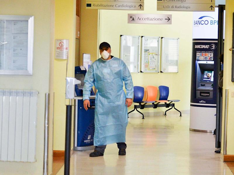 A health worker wearing a face mask walks in a corridor of the Codogno Civic Hospital in Lodi, northern Italy: EPA