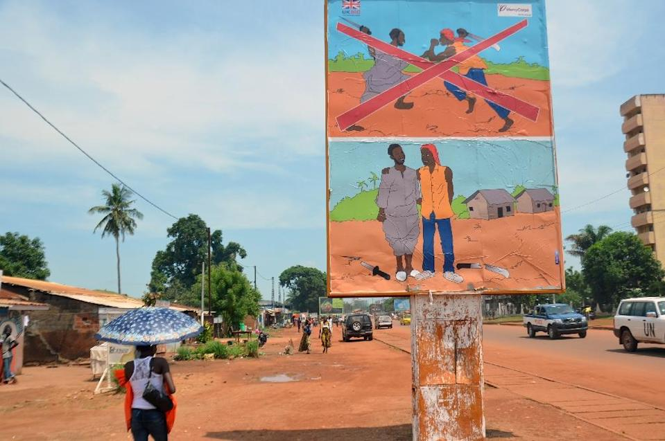 """Let Us Reconcile"" implores a banner on a statue at the entrance to the main market in Bangui, in a Muslim neighbourhood that gave refuge to people fleeing religious strife that swept the Central African Republic (AFP Photo/Patrick Fort)"