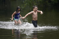 Marina Kingsmill and her brother Raylan play in the flooded street in front of their home after Tropical Storm Claudette passed through in Slidell, La., Saturday, June 19, 2021. The National Hurricane Center declared Claudette organized enough to qualify as a named storm early Saturday, well after the storm's center of circulation had come ashore southwest of New Orleans. (AP Photo/Gerald Herbert)