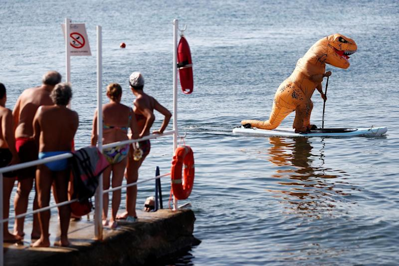 People watch a man wearing a T-Rex costume on a paddle board during hot weather at Sferracavallo beach, in Palermo, Italy (REUTERS)