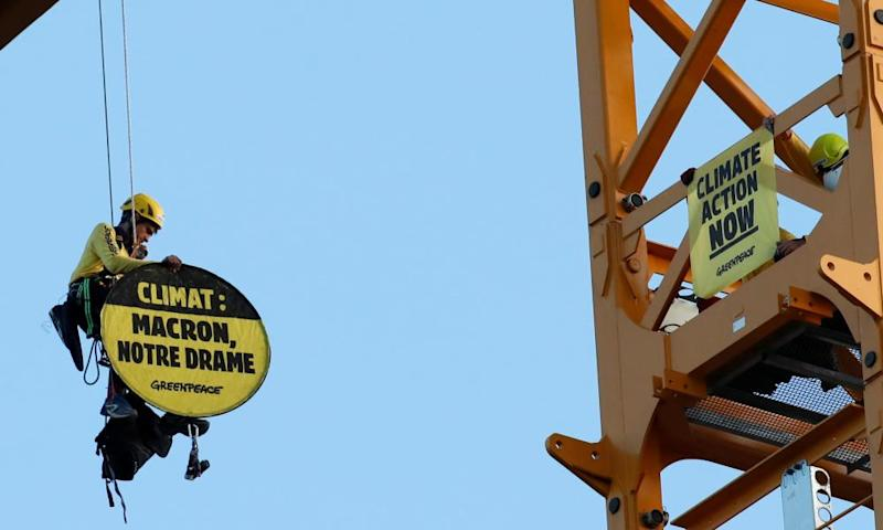 A Greenpeace activist holds a sign reading 'Climate: Macron our drama' while dangling from a crane near Notre-Dame Cathedral in Paris.