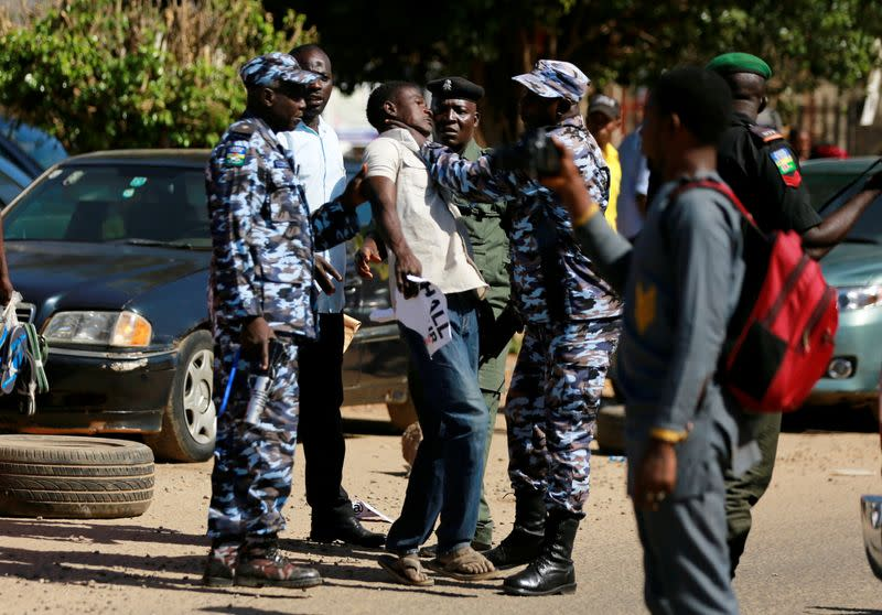 Policemen detain one of the suspected attackers of human rights activist Deji Adeyanju during a freedom rally in Abuja