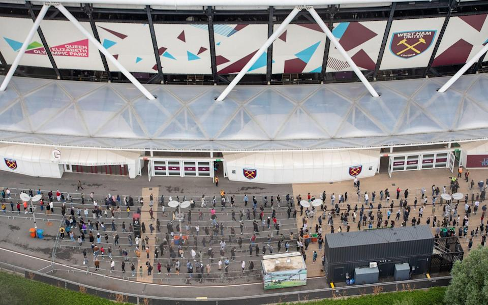 People queue outside an NHS Vaccination Clinic at West Ham's London Stadium in Stratford, east London. - Dominic Lipinski/PA