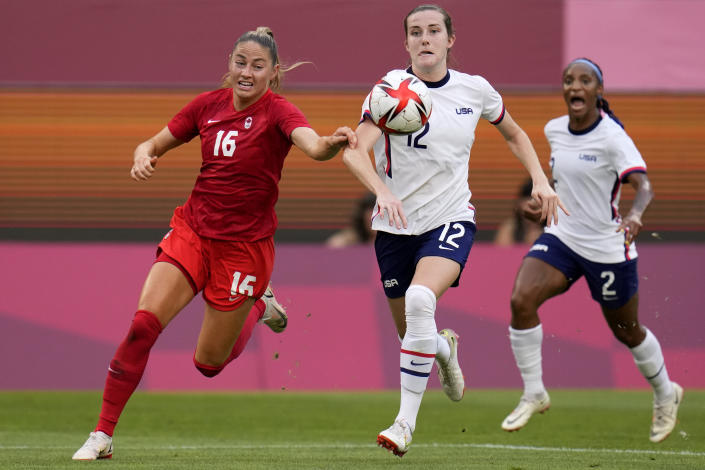 Canada's Janine Beckie, left, and United States' Tierna Davidson battle for the ball during a women's semifinal soccer match at the 2020 Summer Olympics, Monday, Aug. 2, 2021, in Kashima, Japan. (AP Photo/Fernando Vergara)