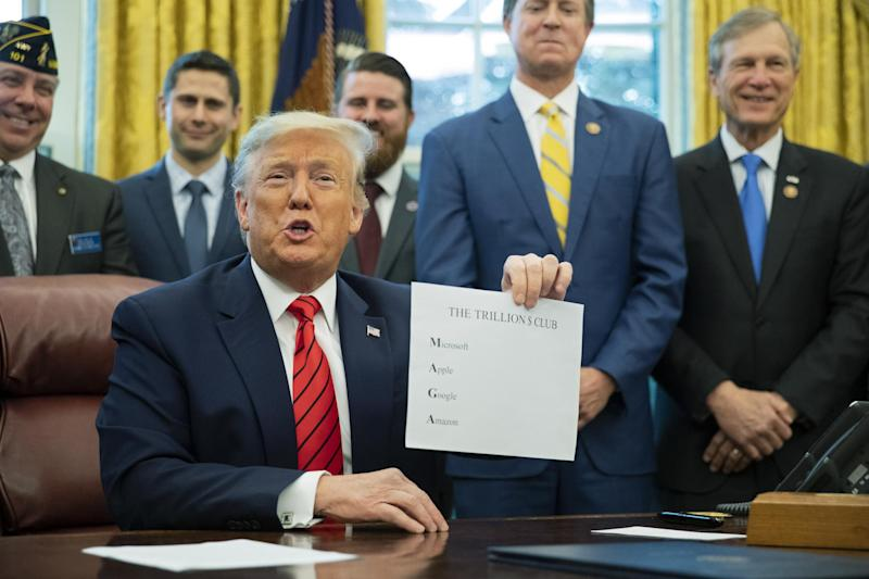 President Donald Trump shows a paper with names of four US companies worth over a trillion dollar to emphasise how good the economy is doing: (AP Photo/Manuel Balce Ceneta)