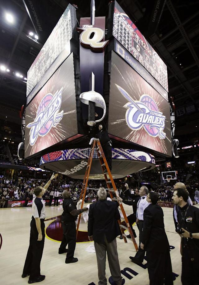Workers look at the scoreboard trying to find a leak before an NBA basketball game between the Cleveland Cavaliers and the Miami Heat on Wednesday, March 20, 2013, in Cleveland. The game was delayed. (AP Photo/Tony Dejak)