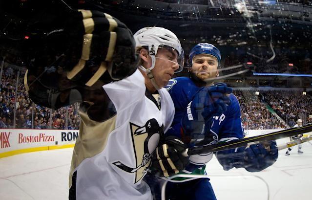 Vancouver Canucks' Zack Kassian, right, checks Pittsburgh Penguins' Matt Niskanen during the first period of an NHL hockey game Tuesday, Jan. 7, 2014, in Vancouver, British Columbia. (AP Photo/The Canadian Press, Darryl Dyck)