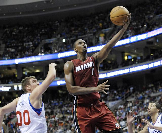 Miami Heat's Chris Bosh (1) drives to the basket past Philadelphia 76ers' Spencer Hawes (00) during the first half of an NBA basketball game, Wednesday, Oct. 30, 2013, in Philadelphia. (AP Photo/Michael Perez)