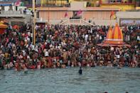 Pilgrims jostled for space along the Ganges before taking a brief plunge in the fast-flowing water and sung hymns and showered flowers into the holy river