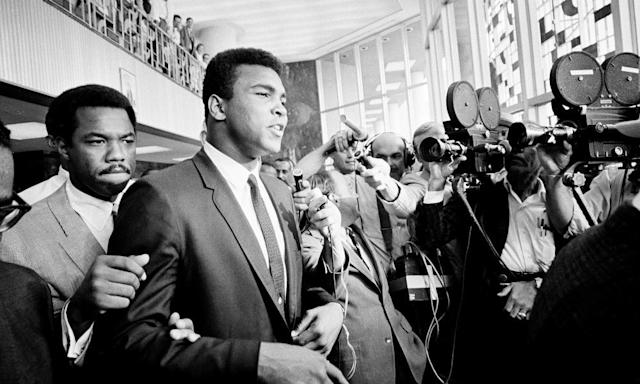 """<span class=""""element-image__caption"""">Muhammad Ali is confronted by journalists as he leaves the Federal Building in Houston for lunch during the noon recess, 19 June 1967. Ali faced trial for refusing to be drafted into the army.</span> <span class=""""element-image__credit"""">Photograph: Ed Kolenovsky/AP</span>"""