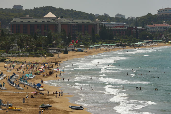 Tourists visit the beach of Antalya, southern Turkey, on Sunday, June 20, 2021. Hotels in Turkey's Antalya region, a destination beloved by holidaymakers, are preparing to finally resume operations as they expect the return of international tourists after months of setbacks caused by the pandemic that halted travel. (AP Photo/Emrah Gurel)