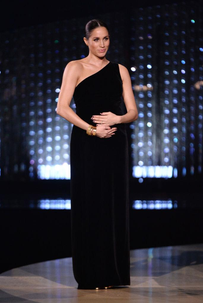 <p>Markle looked elegant in her asymmetrical Givenchy gown and bold gold bracelets during a surprise appearance at the 2018 Fashion Awards to honour friend and designer, Clare Waight Keller. <em>(Image via Getty Images)</em></p>