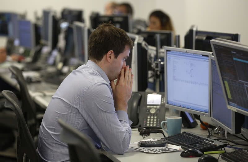 A trader sits at his desk at IG Index in London