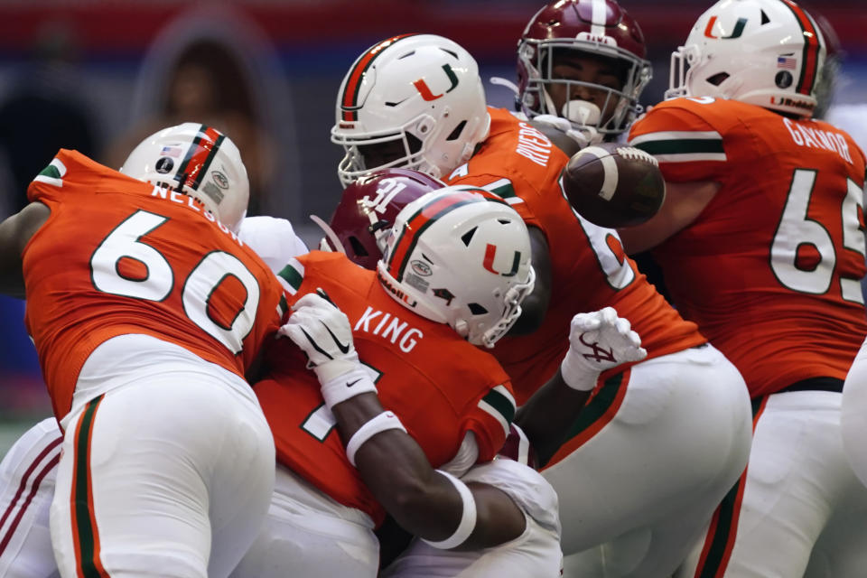Miami quarterback D'Eriq King (1) fumbles as he is sacked by Alabama linebacker Christopher Allen (4) during the first half of an NCAA college football game Saturday, Sept. 4, 2021, in Atlanta. Alabama recovered the ball. (AP Photo/John Bazemore)