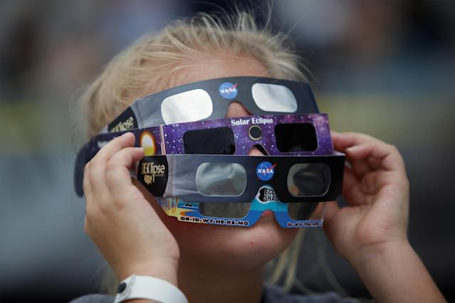 <p>Ariana Mareyev (10) of Charleston wears several pairs of solar glasses on the flight deck of the Naval museum ship U.S.S. Yorktown during the Great American Eclipse in Mount Pleasant, South Carolina, Aug. 21, 2017. (Photo: Randall Hill/Reuters) </p>