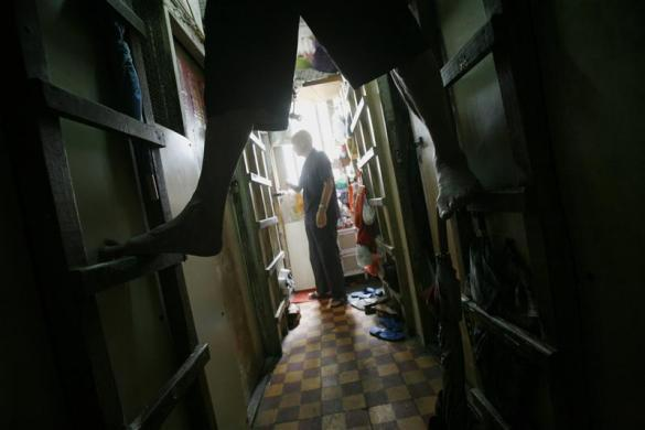 "A man climbs up his ""cubicle"" home, one of the 19 24-square feet units inside a 600 square foot residential apartment complex in Hong Kong September 16, 2009. The Hong Kong government estimates that about 100,000 people live in similar ""cubicle"" units, which cost an average monthly rental rate of $150, in one of the world's largest financial hubs, according to the Society for Community Organization, an NGO which helps those in need."