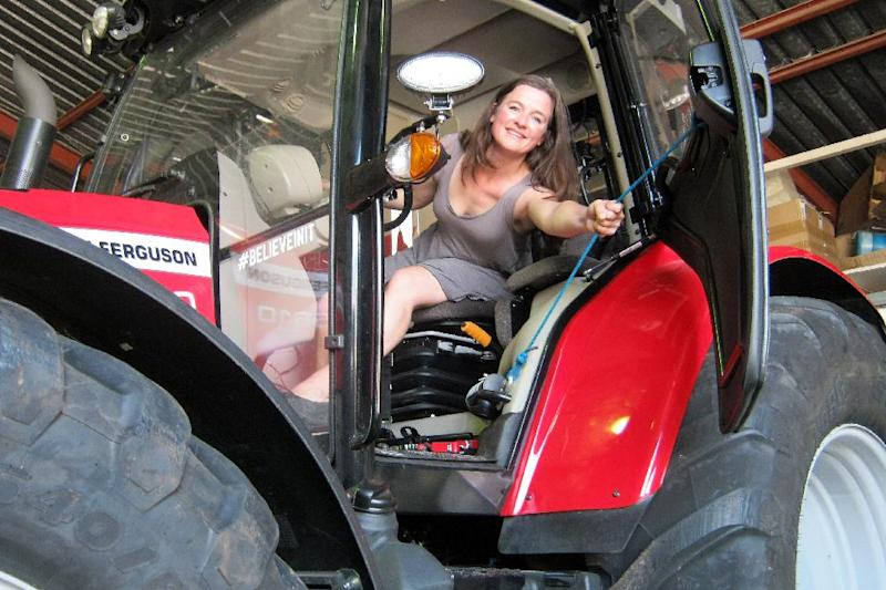 Manon Ossevoort poses inside her tractor at her house on the South African Western Cape on November 9, 2014 (AFP Photo/Lawrence Bartlett)