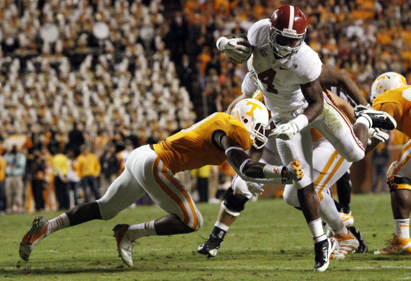 Alabama running back T.J. Yeldon (4) avoids a tackle by Tennessee defensive back Byron Moore (3) during the second quarter of an NCAA college football game on Saturday, Oct. 20, 2012, in Knoxville, Tenn. (AP Photo/Wade Payne)