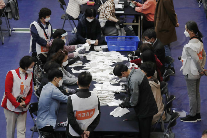 National Election Commission officials sort out ballots for counting at the Seoul mayoral by-election in Seoul, South Korea, Wednesday, April 7, 2021. (AP Photo/Lee Jin-man)