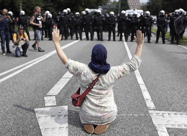 <p>A woman raises her arms as she kneels on a road in front of police officers on the first day of the G-20 summit in Hamburg, northern Germany, Friday, July 7, 2017. (Photo: Matthias Schrader/AP) </p>