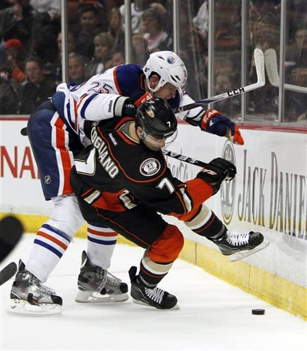 Edmonton Oilers defenseman Andy Sutton (25) collides with Anaheim Ducks center Andrew Cogliano (7) in the second period of an NHL hockey game in Anaheim, Calif., Sunday, April 1, 2012. (AP Photo/Christine Cotter)