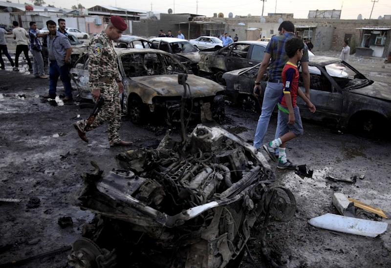 Iraqis gather at the scene of a car bomb attack at a used cars dealers parking lot in Habibiya neighborhood of eastern Baghdad, Iraq, Monday, May 27, 2013. A wave of car bombings tore through mostly Shiite Muslim neighborhoods of the Baghdad area, killing and wounding dozens of people, police said, in the latest outburst of an unusually intense wave of bloodshed roiling Iraq. The blasts are the latest indication that Iraq's security is rapidly deteriorating. (AP Photo/ Karim Kadim)