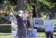 Fifth Congressional District Democratic candidate Antone Melton-Meaux, left, waves to passing cars in south Minneapolis Tuesday, Aug. 11, 2020, primary Election Day in Minnesota. He faces Democratic, Rep. Ilhan Omar in the primary. (AP Photo/Jim Mone)