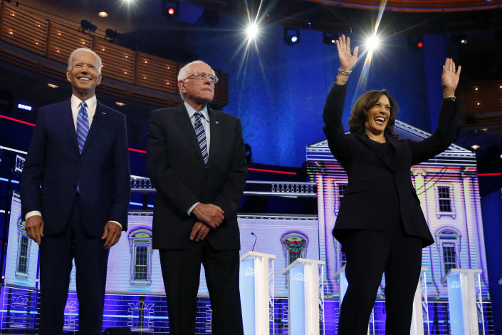 Democratic presidential candidates former vice president Joe Biden, left, Sen. Bernie Sanders, I-Vt., and Sen. Kamala Harris, D-Calif., right, stand on stage for a photo op before the start of the the Democratic primary debate hosted by NBC News at the Adrienne Arsht Center for the Performing Arts, Wednesday, June 27, 2019, in Miami. (AP Photo/Wilfredo Lee)