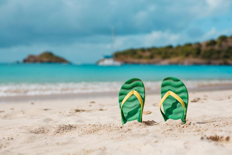 Green flipflops in the white sandy beach near sea waves, nobody. Summer vacation concept with blue water. Relax, vacation on tropical island. Copyspace