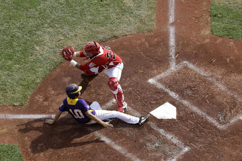 Aguadulce, Panama's Jean Mar Sanchez, left, scores past Tijuana, Mexico's Saul Favela on a sacrifice fly by Jordan Agrazal during the second inning of an elimination baseball game at the Little League World Series, Thursday, Aug. 22, 2013, in South Williamsport, Pa. (AP Photo/Matt Slocum)