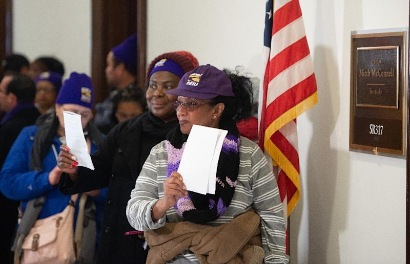 Furloughed US federal workers who have not been paid during the partial government shutdown have protested on Capitol Hill -- here, some hold their unpaid bills to present to the office of Senate Majority Leader Mitch McConnell (AFP Photo/SAUL LOEB)