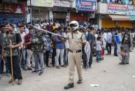 Police officers stand guard as people attend a protest against the alleged rape and murder of a 27-year-old woman in Shadnagar