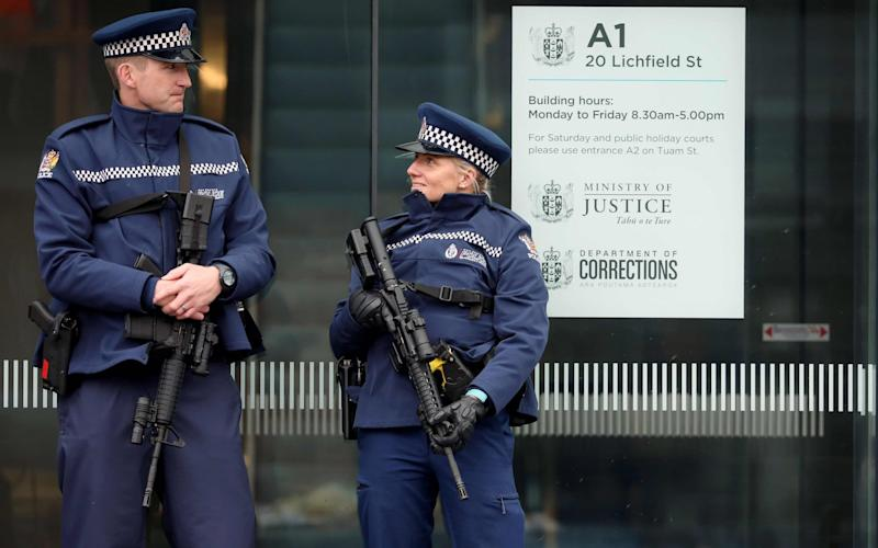 Armed police officers stand guard outside the Christchurch District Court in Christchurch - AFP