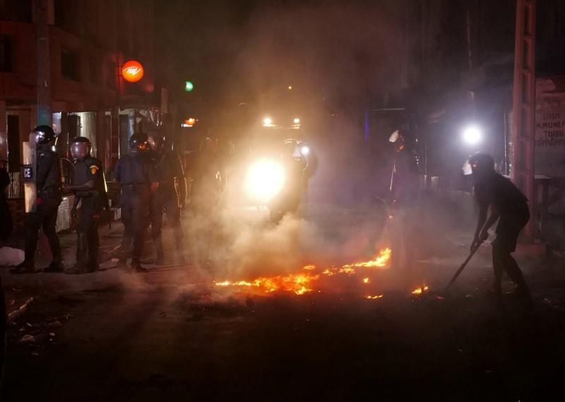 Riot police try to put out fire in the middle of the street during protests in Dakar