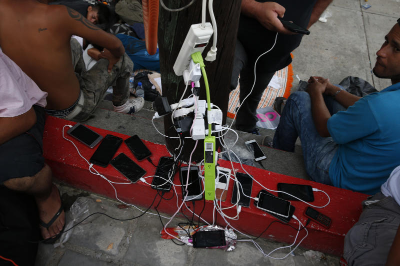 FILE - In this Oct. 28, 2018 file photo, migrants charge their cell phones as a caravan of Central Americans trying to reach the U.S. border halts for a rest day in San Pedro Tapanatepec, Oaxaca state, Mexico. Hundreds of Central Americans are now getting as many details as possible before leaving north towards the U.S. border. Increasingly they're organized over Facebook and WhatsApp as they try to join together in large groups they hope will make the trip safer, and without having to hide themselves from authorities. (AP Photo/Rebecca Blackwell, File)