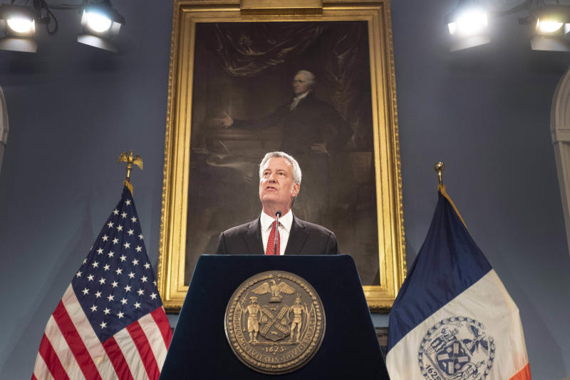 FILE - In this Aug. 2, 2019 file photo, New York Mayor Bill de Blasio speaks at a news conference in New York. The New York City Seal appears on the podium that de Blasio speaks from as well as on one of the flags behind him. De Blasio said on Monday, July 27, 2020 that he would be in favor of re-examining if the city seal holds up to contemporary scrutiny after a founding member of a Native American group said the Native American man shown on the seal is