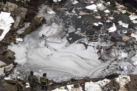 Firefighters stand next to leaking oil at a stream a day after an explosion at a Sinopec Corp oil pipeline in Huangdao, Qingdao, Shandong Province November 23, 2013. REUTERS/Aly Song
