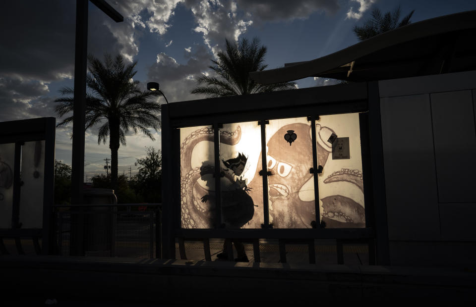 A man waits at a bus stop as the sun sets Friday, Sept. 10, 2021, in Las Vegas. Soaring temperatures fueled by climate change are making it harder to live in the United States' already hot, fast growing desert counties like Nevada's Clark County, home to Las Vegas. (AP Photo/John Locher)