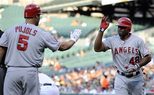 Los Angeles Angels' Torii Hunter (48) celebrates his home run with teammate Albert Pujols (5) during the first inning of a baseball game against the Baltimore Orioles, Wednesday, June 27, 2012, in Baltimore. (AP Photo/Nick Wass)