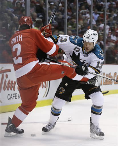 Detroit Red Wings defenseman Brendan Smith (2) checks San Jose Sharks left wing Raffi Torres (13) during the first period of an NHL hockey game in Detroit, Thursday, April 11, 2013. (AP Photo/Carlos Osorio)