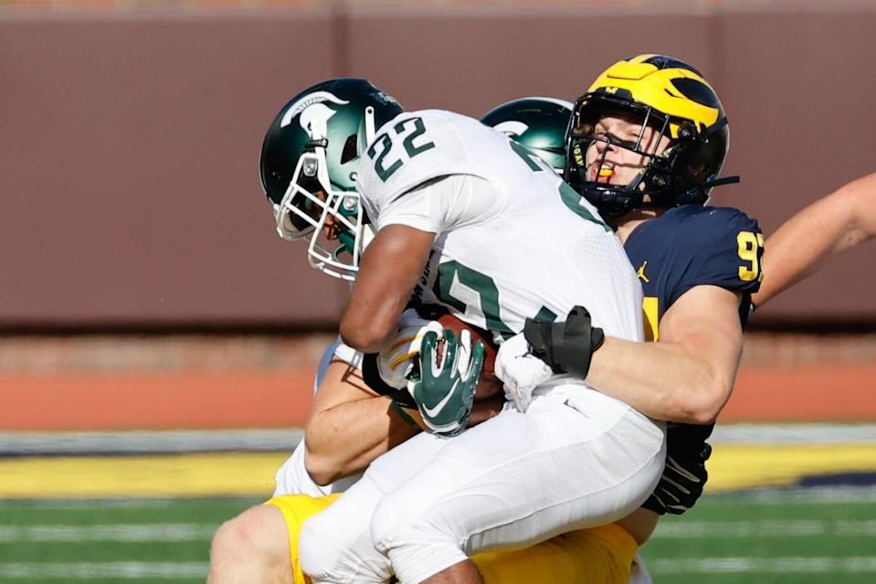 Michigan State running back Jordon Simmons is tackled by Michigan defensive lineman Aidan Hutchinson in the first half on Oct. 31, 2020, at Michigan Stadium.