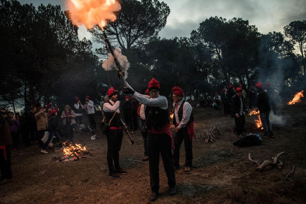 <p>A 'Galejador' fires his musket during 'la Festa del Pi' (The Festival of the Pine) in Centelles, Spain. Early in the morning men and women born in Centelles, who are named 'Galejadors' wear their traditional costume with the Catalan red hat known as 'Barretina' and carry their shooting muskets as they walk into the forest to chop down a pine tree, load it on an ox cart and take it to the church in the village. The pine tree is decorated with five bouquets of apples and wafers and hung inside a church until January 6. The tradition has been documented since 1751 and it is believed its origins are related to the trees and the pagan worship of fertilization related to the winter solstice. (David Ramos/Getty Images) </p>