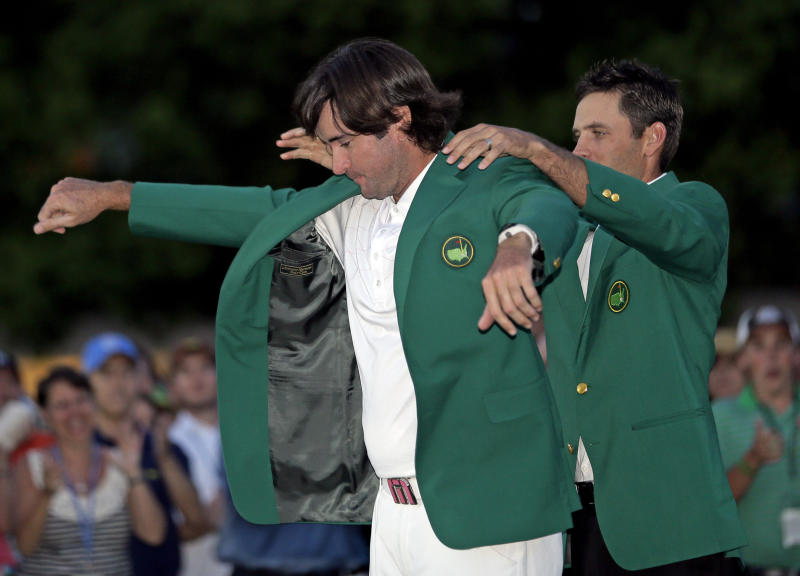 Charl Schwartzel, right, of South Africa, helps Bubba Watson put on the green jacket after winning the Masters golf tournament following a sudden death playoff on the 10th hole Sunday, April 8, 2012, in Augusta, Ga. (AP Photo/David J. Phillip)